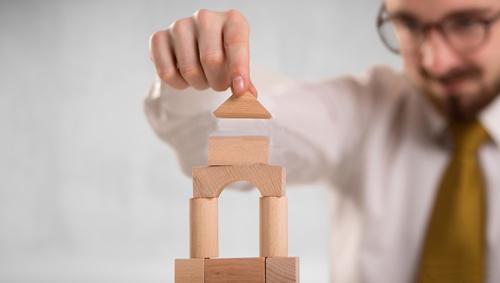 Estratégia de negócios simbolizada por um executivo montando uma torre de brinquedo